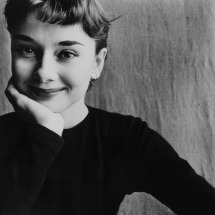 Actress Audrey Hepburn wearing a black crew neck sweater, smiling, and resting her chin in her hand